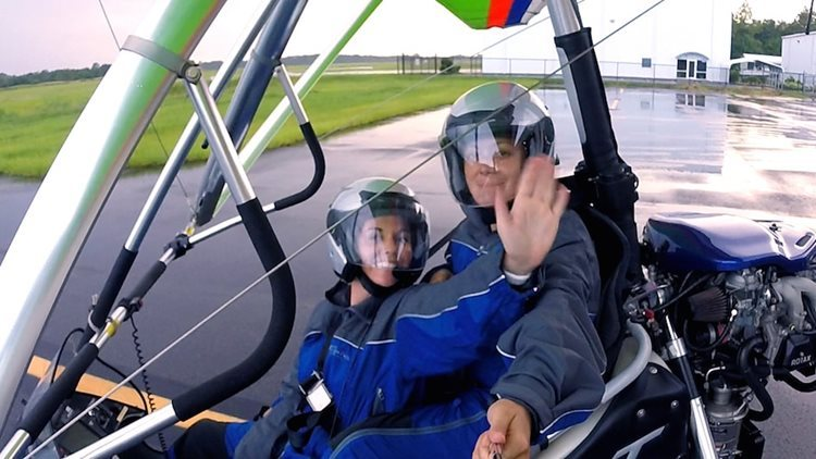 couple on a runway sitting in a para glider