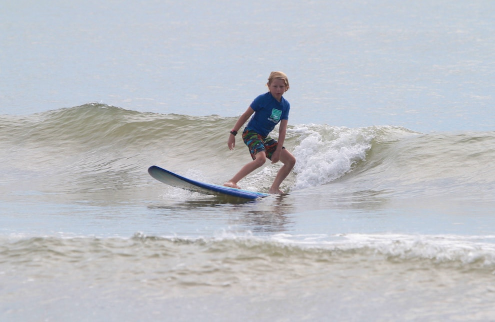 a boy surfing on a wave
