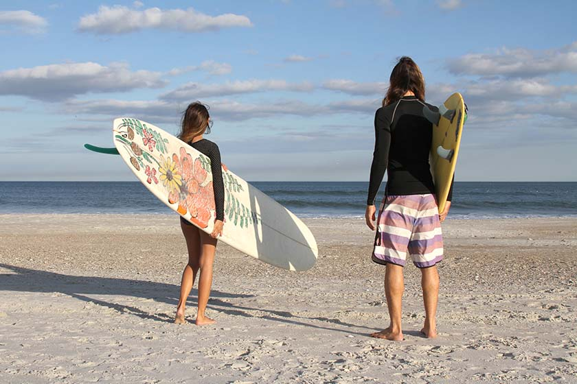 a member of surf school with their instructor standing on the beach